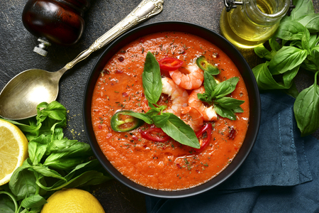 Delicious tomato soup with shrimps in a black bowl over dark slate, stone or concrete background. Top view with copy space.