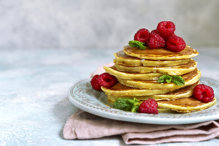 Stack of delicious homemade hot pancakes with honey and fresh raspberry on a vintage plate on a light slate, stone or concrete background.