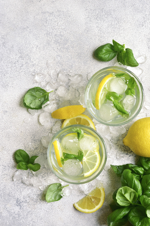 Homemade summer basil lemonade in a glasses over light slate, stone or concrete background.Top view with copy space. Фото со стока