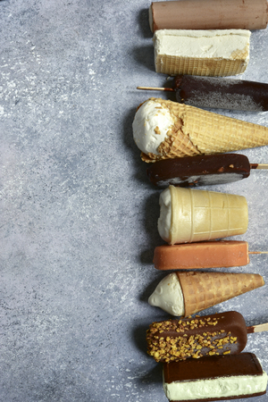 Assortment of ice cream on a grey slate, stone or concrete background. Top view with copy space.