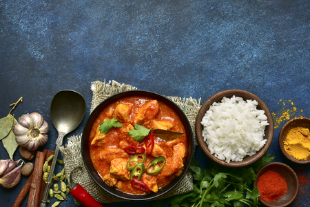 Chicken tikka masala - traditional dish of indian cuisine in a clay bowl over dark blue slate, stone or concrete background.Top view with copy space. Stockfoto - 117540941