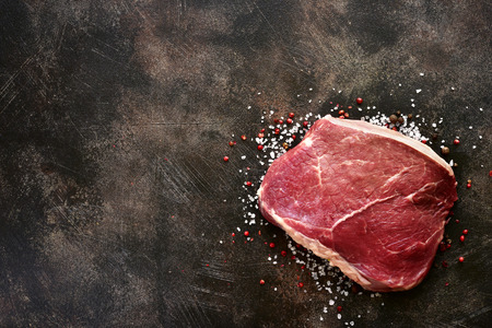 Fresh raw marbled beefsteak with spices and salt on a dark slate, stone, metal or concrete background.Top view with copy space.