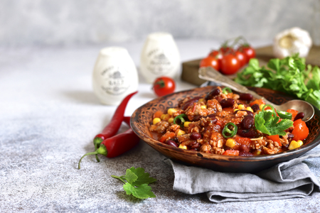 Chili con carne - minced meat stew with red bean and tomato in a clay bowl on a light grey slate, stone or concrete background.Traditional dish of mexican cuisine. Banque d'images