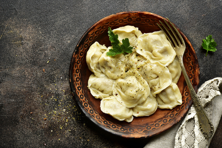 Traditional russian dish pelmeni - dumplings stuffed with minced meat in a clay bowl over dark slate, stone or concrete background.Top view with copy space.