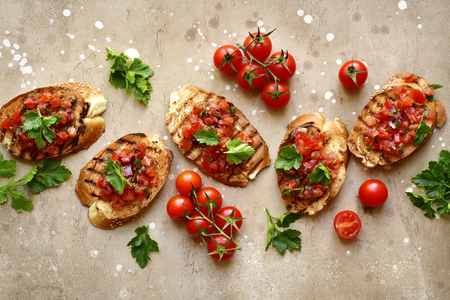 Tostadas con tomates cherry, cebolla morada y aceite de oliva sobre un fondo beige o arena de pizarra, piedra u hormigón.Vista superior con espacio de copia.