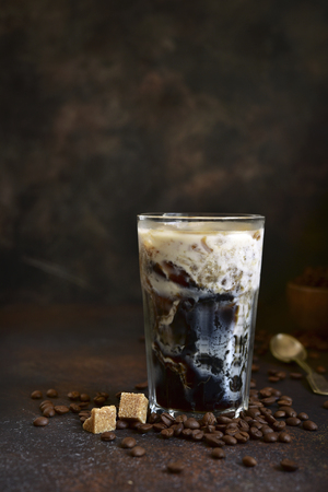 Homemade delicious iced coffee in a tall glass on a dark slate, stone or concrete background. Stock Photo