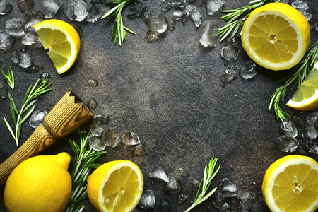 Food background with ingredients for making summer citrus lemonade or cocktail on a dark slate, stone or concrete backdrop. Top view with copy space.