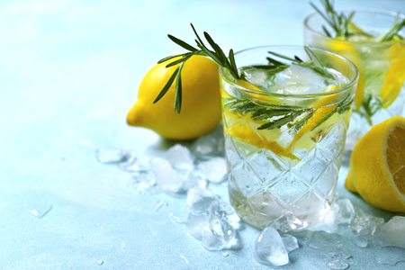 Summer citrus cocktail or lemonade with rosemary in a glasses on a light blue slate, stone or concrete background. Top view with copy space. Stock fotó