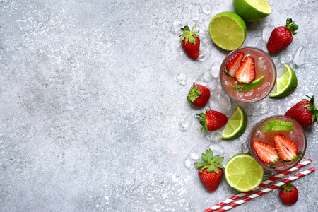 Homemade strawberry lemonade with lime in a glasses on a light grey slate, stone or concrete background. Top view with copy space.