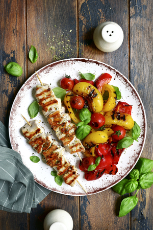Grilled chicken skewers kebab with roasted vegetables on a white plate over dark rustic wooden background.Top view with copy space.
