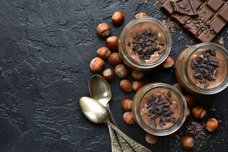 Homemade chocolate hazelnut mousse in a vintage glasses on a black slate, stone or concrete background. Top view with copy space.