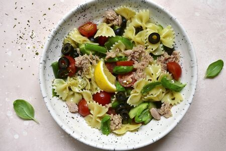 Pasta salad with tuna and vegetables in a white bowl over light slate, stone or concrete background. Top view with copy space.