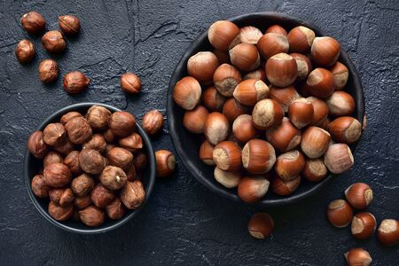 Peeled and unpeeled hazelnuts in a bowl over dark slate, stone or concrete background.Top view with copy space. Stockfoto