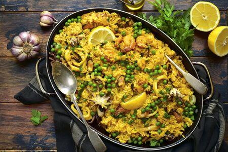 Classic valencian paella from rice with seafood and vegetables - traditional dish of spanish cuisine in a frying pan on a light slate, stone or concrete background.Top view with copy space.