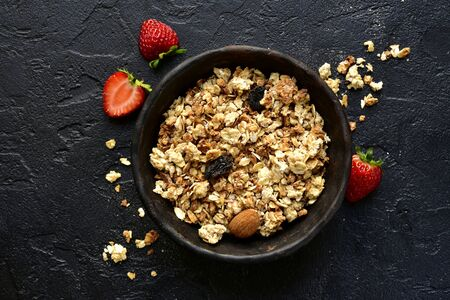 Homemade multicereal granola with fresh strawberry in a black bowl over dark slate, stone or concrete background. Top view with copy space.