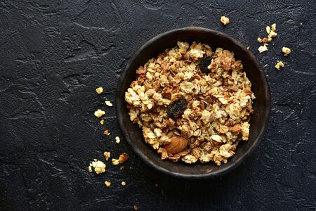 Homemade multicereal granola in a black bowl over dark slate, stone or concrete background. Top view with copy space.