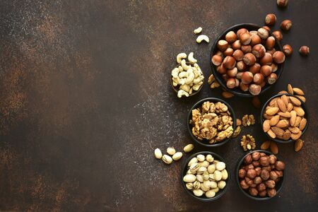 Assortment of nuts in a bowls on  a dark slate or stone background - healthy snack.Top view with copy space .