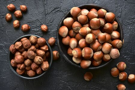 Peeled and unpeeled hazelnuts in a bowls over black slate, stone or concrete  background.Top view with copy space. Stockfoto