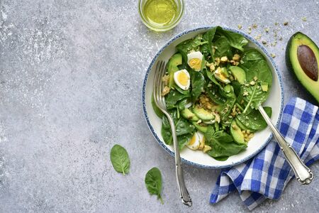Green vegetable salad with baby spinach, avocado, walnut and egg in a bowl on a light grey slate, stone or concrete background. Top view with copy space.