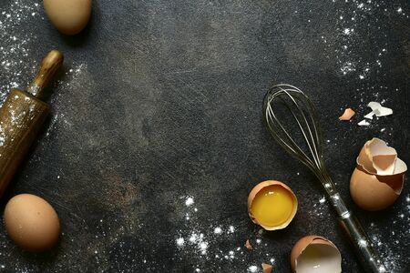 Culinary background with ingredients for baking : milk, butter,sugar, dough and egg on a dark slate, stone or concrete table. Top view with copy space. Stock fotó