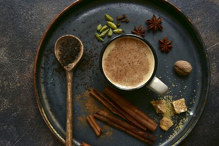 Traditional indian masala tea with ingredients for making on a dark slate, stone or concrete background. Top view with copy space. Stockfoto