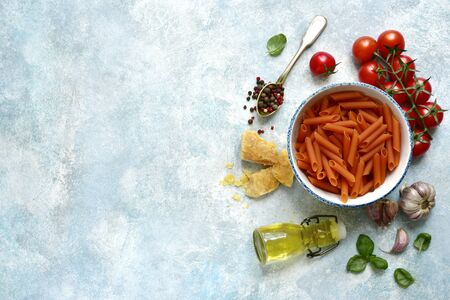 Traditional ingredients of italian cuisine : pasta penne, tomato, garlic, olive oil, parmesan cheese and basil on a light blue slate, stone or concrete background. Top view with copy space.