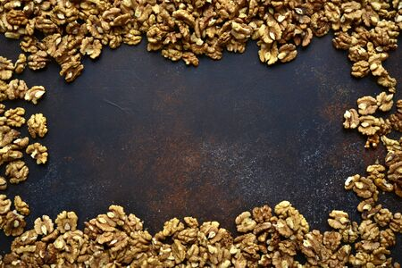 Heap of raw peelled organic walnuts on a dark slate, stone or concrete background. Top view with copy space. Stockfoto