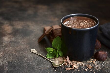 Homemade hot chocolate with mint in a black mug on a dark slate, stone or concrete background.
