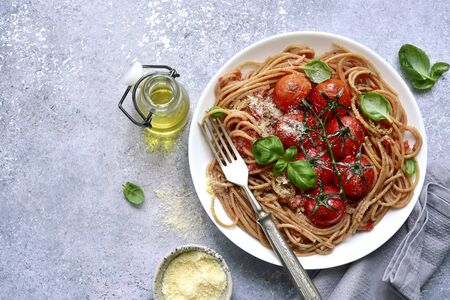 Whole grain spaghetti pasta with grilled cherry tomato in a white bowl over light grey slate, stone or concrete background.Top view with copy space.