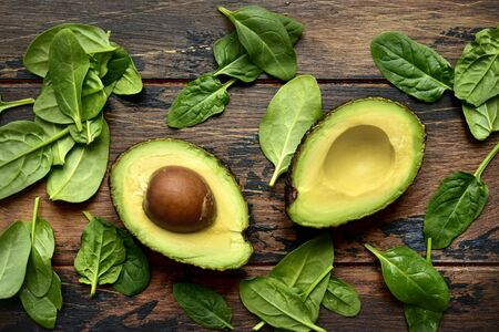 Halves of fresh raw avocado with baby spinach leaves on a dark wooden background Top view with copy space.