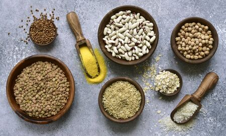 Assortment of grains, cereals and legumes in a bowls on a light grey slate, stone or concrete background. Top view with copy space. Stockfoto