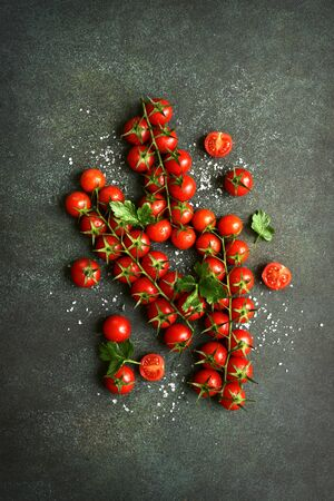 Fresh ripe cherry tomatoes on a bunchs on a dark green slate, stone or concrete background. Top view with copy space.