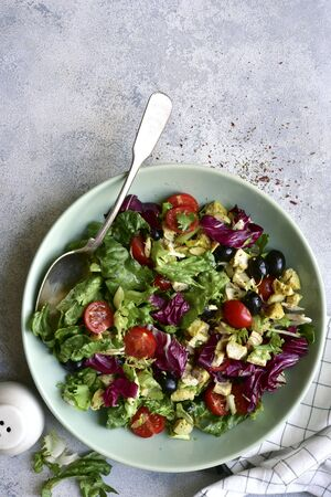 Vegetable salad with griklled chicken in a bowl on a light grey slate, stone or concrete background. Top view with copy space.