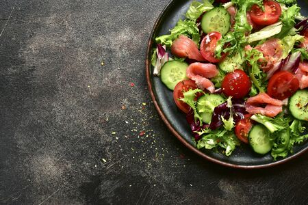 Vegetable salad with salmon and salad leaves mix on a plate on a dark slate, stone or concrete background. Top view with copy space. Stockfoto