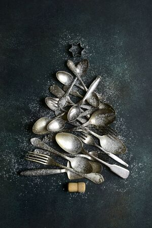 Abstract christmas tree made from old vintage cutlery on a dark green ( emerald ) slate, stone or concrete background. Top view with copy space.