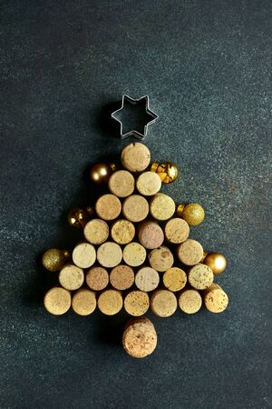 Abstract christmas tree made from wine bottle caps on a dark green slate, stone or concrete background. Top view with copy space.
