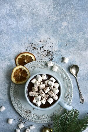 Homemade festive hot chocolate with cinnamon and orange in a blue vintage cup over light slate, stone or concrete background. Top view with copy space.
