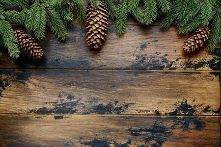 Fir tree branches and pine cones on a dark wooden background. Top view with copy space. Stockfoto