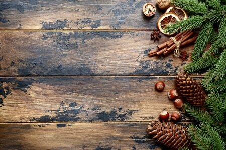 Fir tree branches, pine cones and christmas spices on a dark wooden background. Top view with copy space.