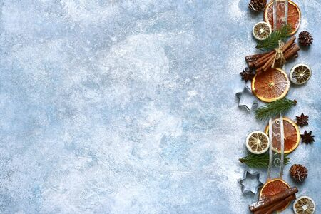 Festive christmas border made frome winter spices and candied fruits on a light blue slate, stone or concrete background. Top view with copy space. Stockfoto