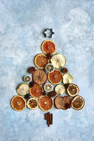 Abstract christmas tree made from candied fruits and winter spices on a light blue slate, stone or concrete background. Top view with copy space.