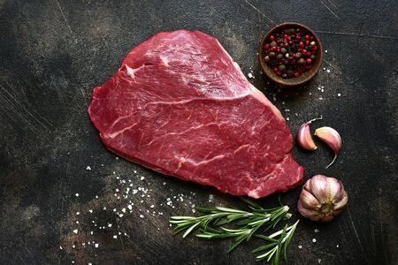 Surowy stek wołowy z przyprawami na ciemnym tle łupkowym, kamiennym lub betonowym. Widok z góry z miejsca na kopię.