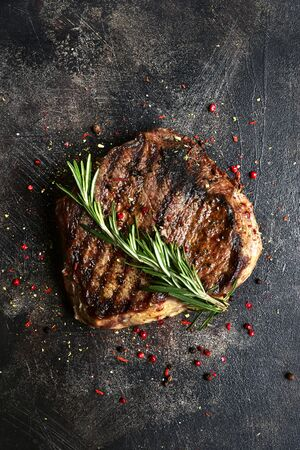Roasted beef steak on a dark slate, stone, concrete or metal background. Top view with copy space.