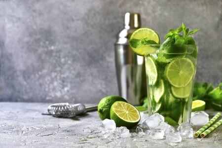 Cytrusowy koktajl mojito z limonką i miętą w wysokiej szklance na jasnoszarym tle łupkowym, kamiennym lub betonowym.
