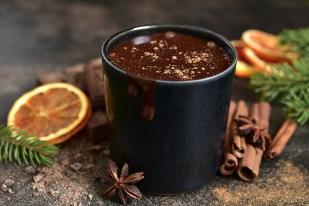 Homemade christmas hot chocolate with orange and spices in a black mug on a dark slate, stone or concrete background. Фото со стока