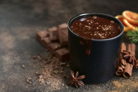Homemade christmas hot chocolate with orange and spices in a black mug on a dark slate, stone or concrete background. 版權商用圖片