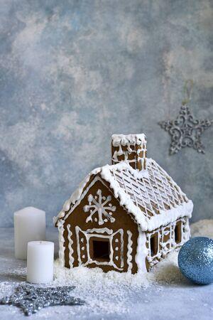 Festive gingerbread house on a light blue slate, stone or concrete background.