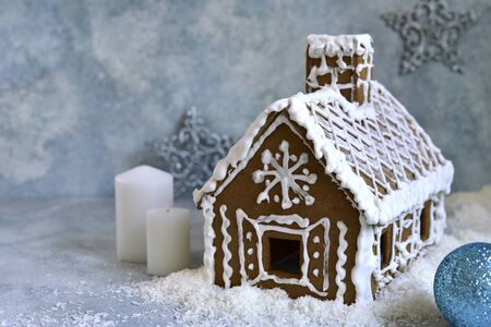 Festive gingerbread house on a light blue slate, stone or concrete background.