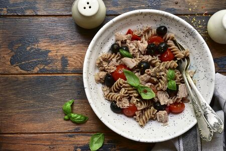 Whole wheat pasta fusilli with tuna, tomato and black olives in a white bowl on a dark wooden background. Top view with copy space. Фото со стока