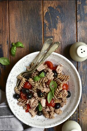 Whole wheat pasta fusilli with tuna, tomato and black olives in a white bowl on a dark wooden background. Top view with copy space. 写真素材